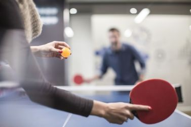 two-colleagues-playing-table-tennis-in-office-break-room-673117017-592611993df78cbe7e959740