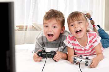 Young-boy-and-girl-lying-on-a-bed-enjoying-playing-video-games-together